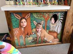 Three Children Posing For the Camera and a Turtle on Wood Plank